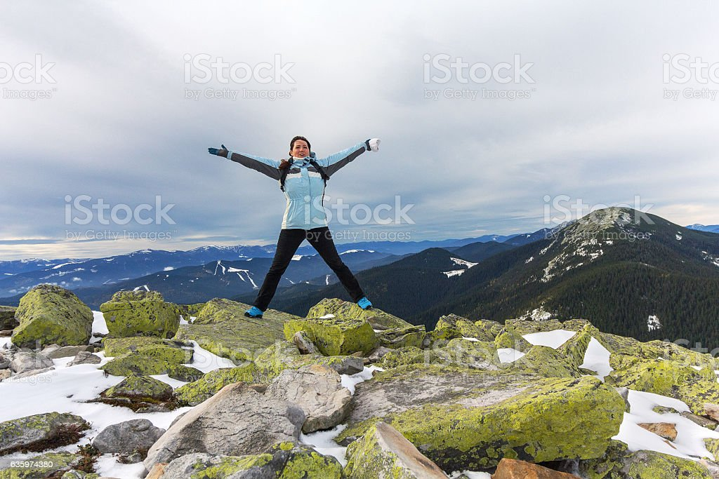 Girl-tourist expresses positive emotions on top of a snowy mountain stock photo