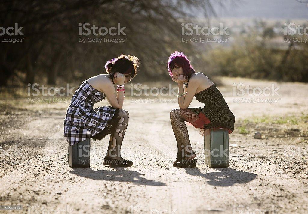 Girsl waiting on a rural road stock photo