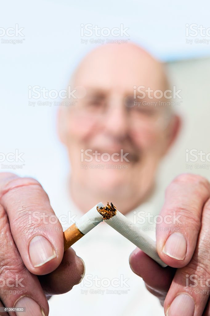 Give up smoking; it's never too late! Senior snaps cigarette. stock photo