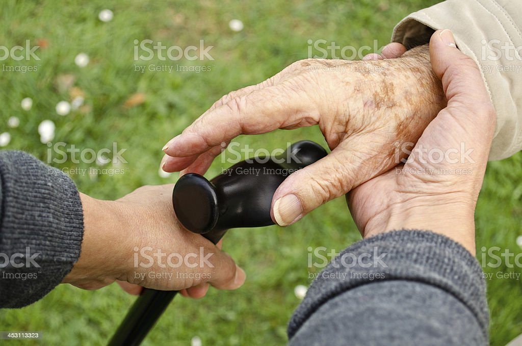Giving a cane to an senior adult. stock photo