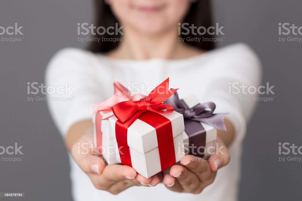 Woman holding a small gift box in a gesture of giving. Christmas...
