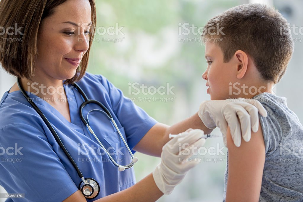 Giving a Vaccine to a Little Boy stock photo