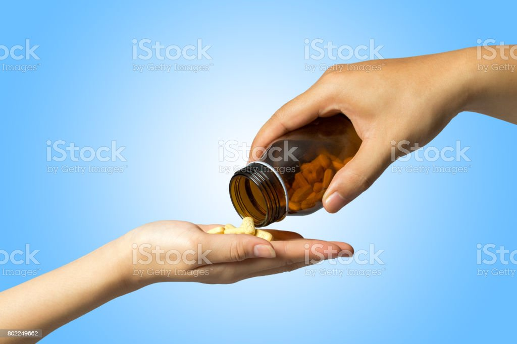 giving drugs hand to hand, blue background. stock photo