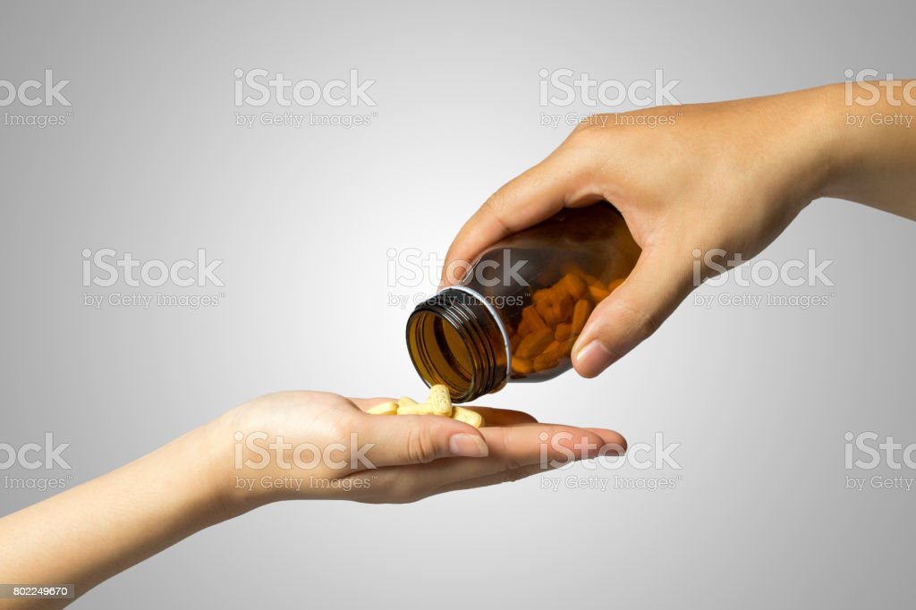 giving drugs hand to hand, grey background. stock photo