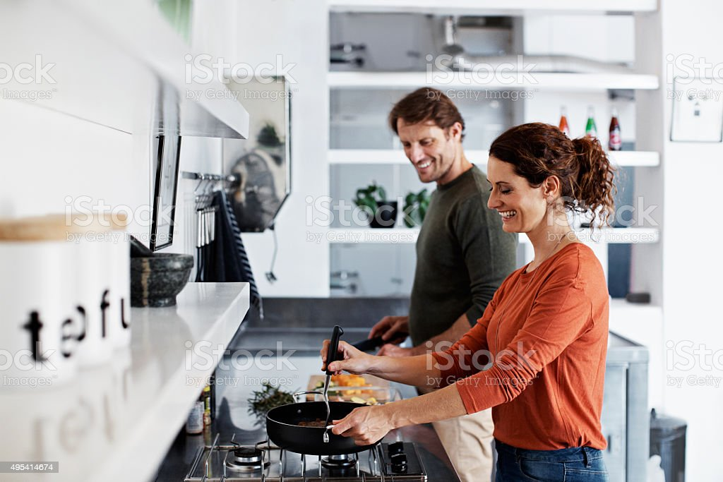 Giving him a lesson or two in cooking stock photo