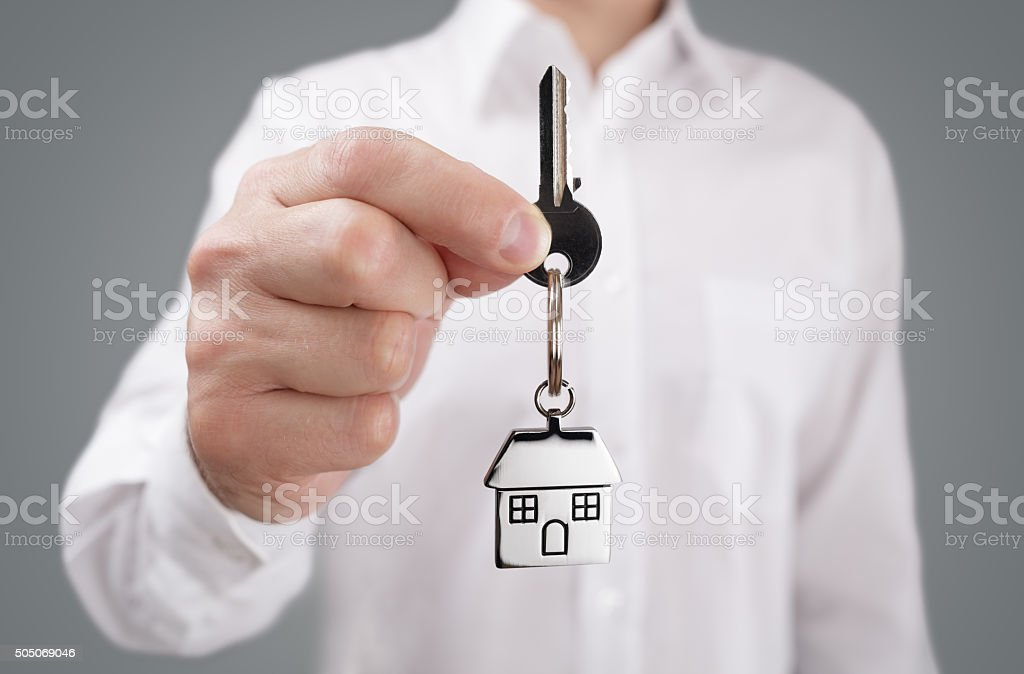 Giving house key on keychain stock photo