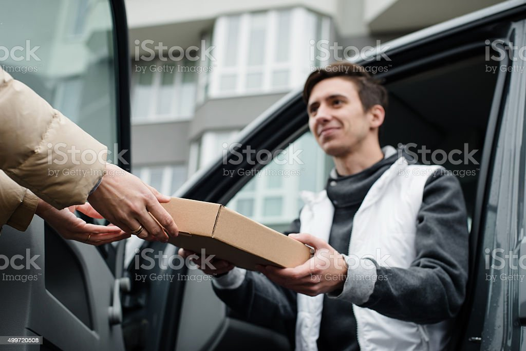 Giving postal box by smiling courier into woman's hands stock photo