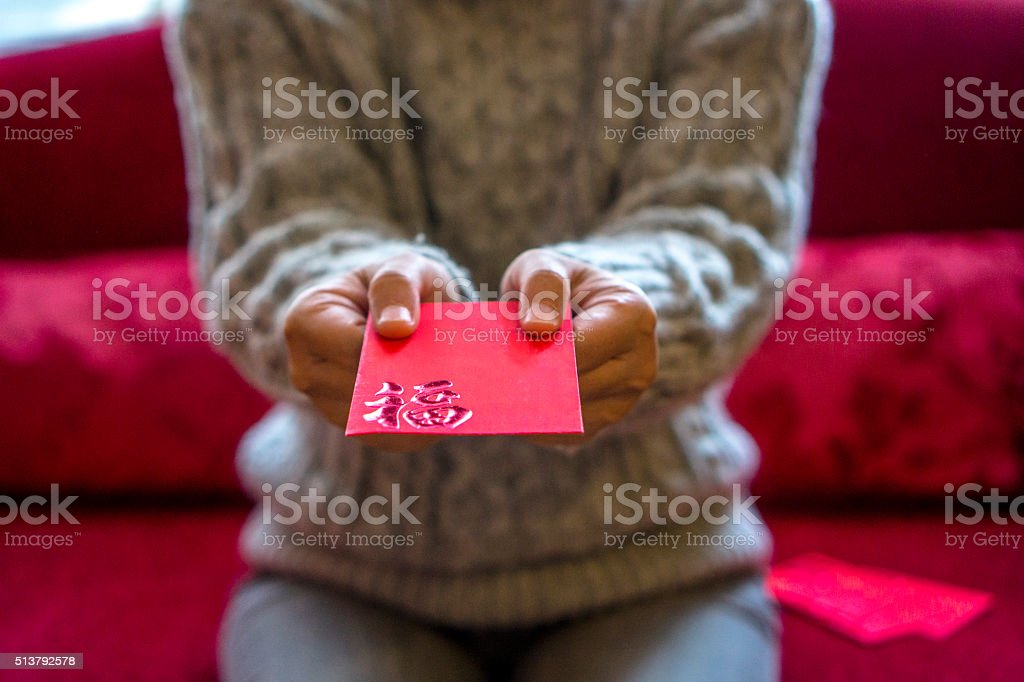 giving red envelope of money on holiday stock photo