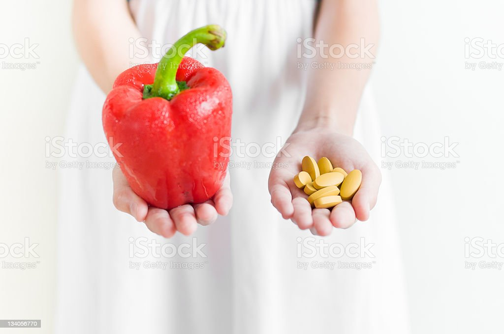 Giving vegetable and  vitamin pill royalty-free stock photo