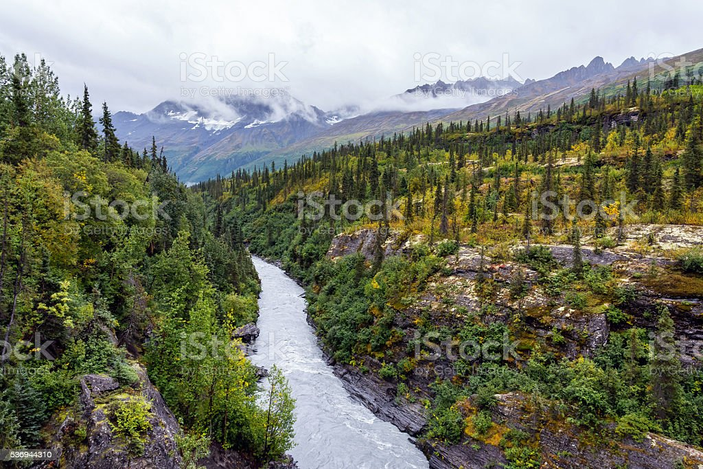 Glacial river cuts through narrow mountain valley stock photo