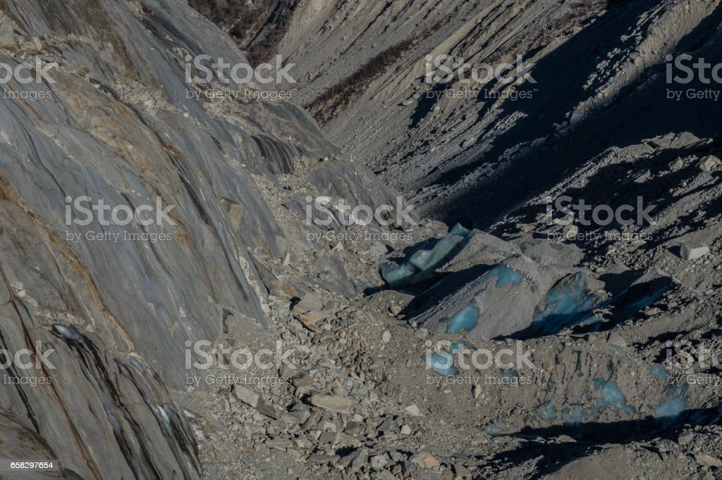 Glacier ice blocks covered by rocks and earth stock photo