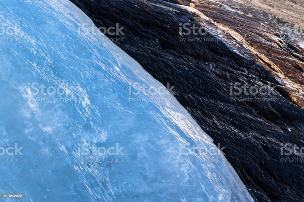 Glacier ice flowing down a rockface with melting water stock photo