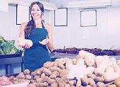 Glad female seller holding yellow gourd