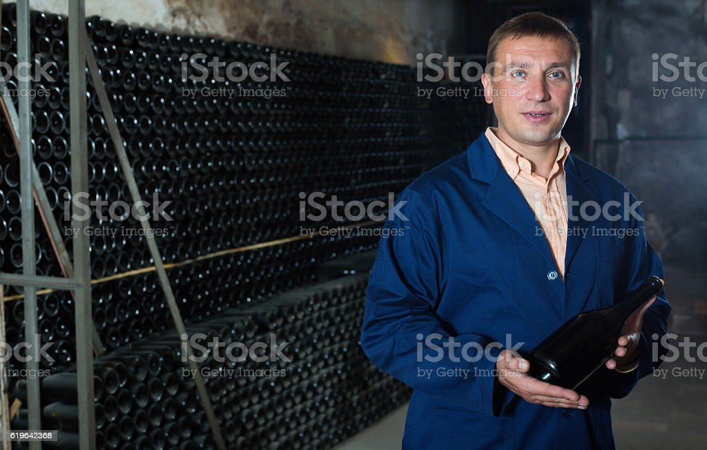 Glad male winery technician posing with bottle stock photo