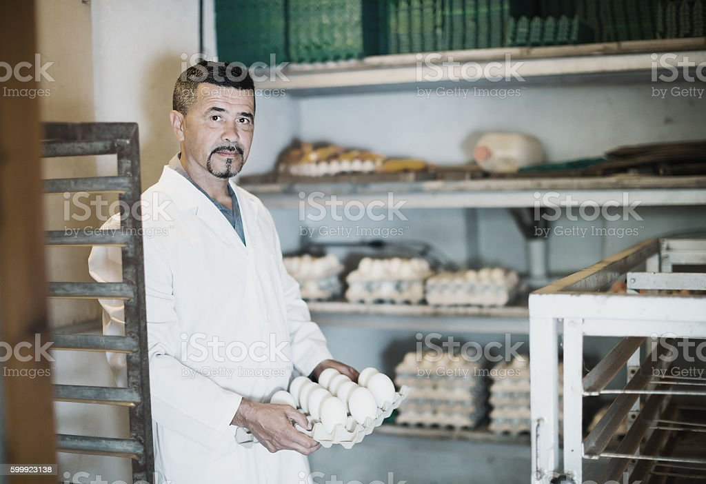 Glad man working and packing white hen eggs stock photo