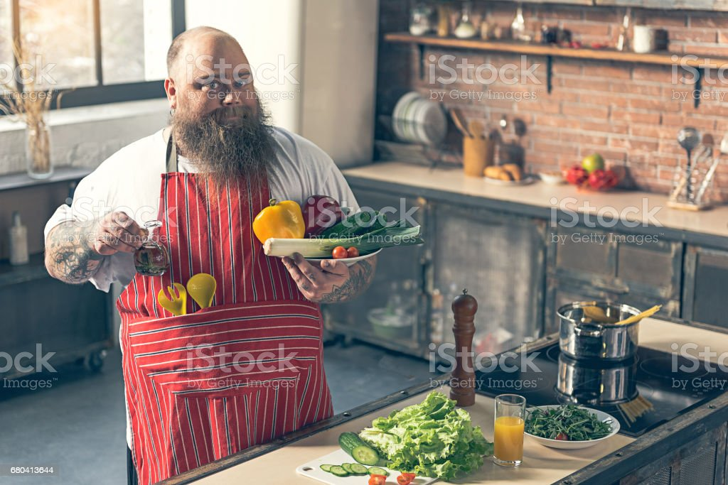 Positive male fat chef is cooking healthy food with enjoyment. He is...