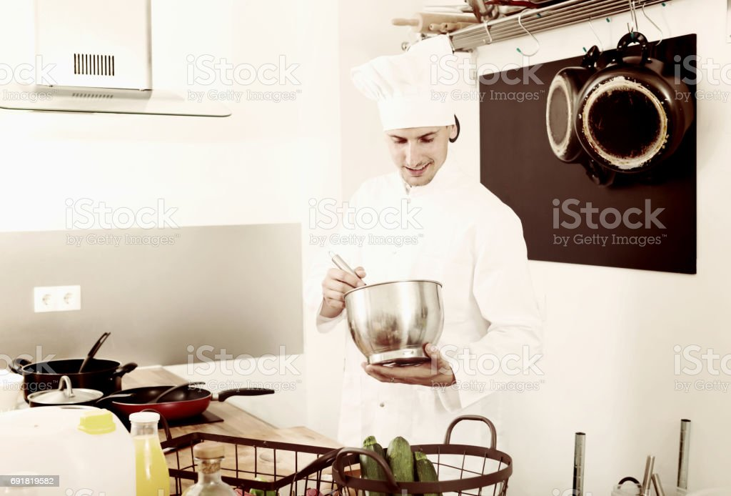 Glad young man chef cooking food at kitchen stock photo