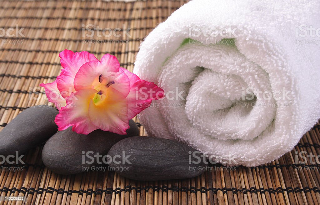 gladiola,black pebbles and white towel on bamboo mat royalty-free stock photo