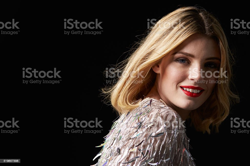 Glamorous blonde woman turning to camera, head shoulders stock photo