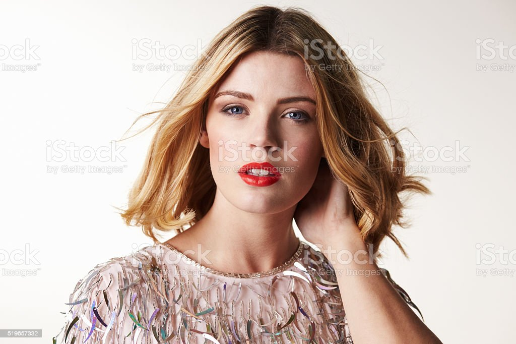 Glamorous blonde woman with hand in hair, looking to camera stock photo