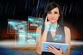Glamorous brunette using tablet pc with interfaces