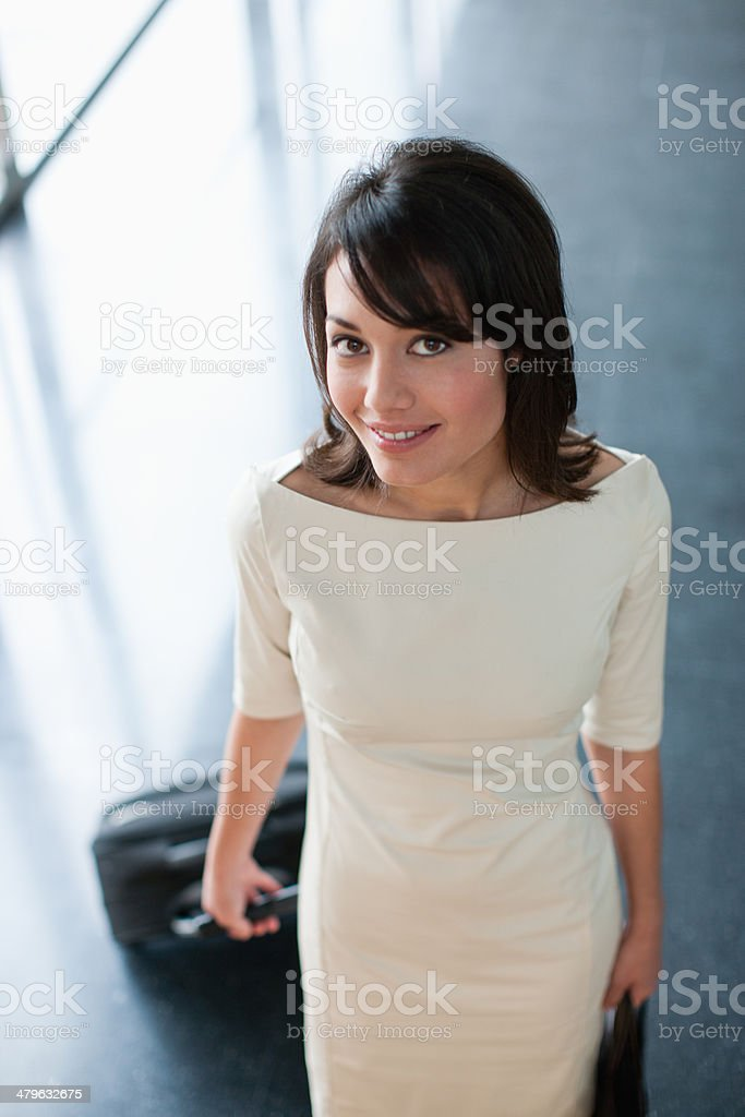 Glamorous businesswoman pulling suitcase stock photo
