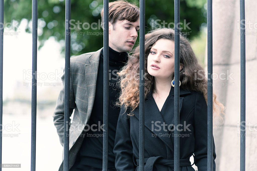 Glamorous couple behind bars outdoors stock photo