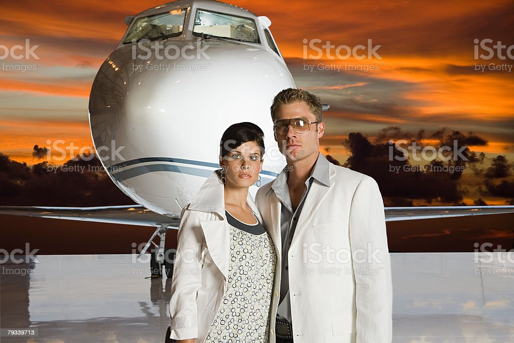 Glamorous couple by jet stock photo