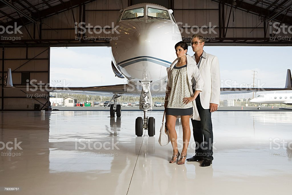 Glamorous couple in hangar stock photo