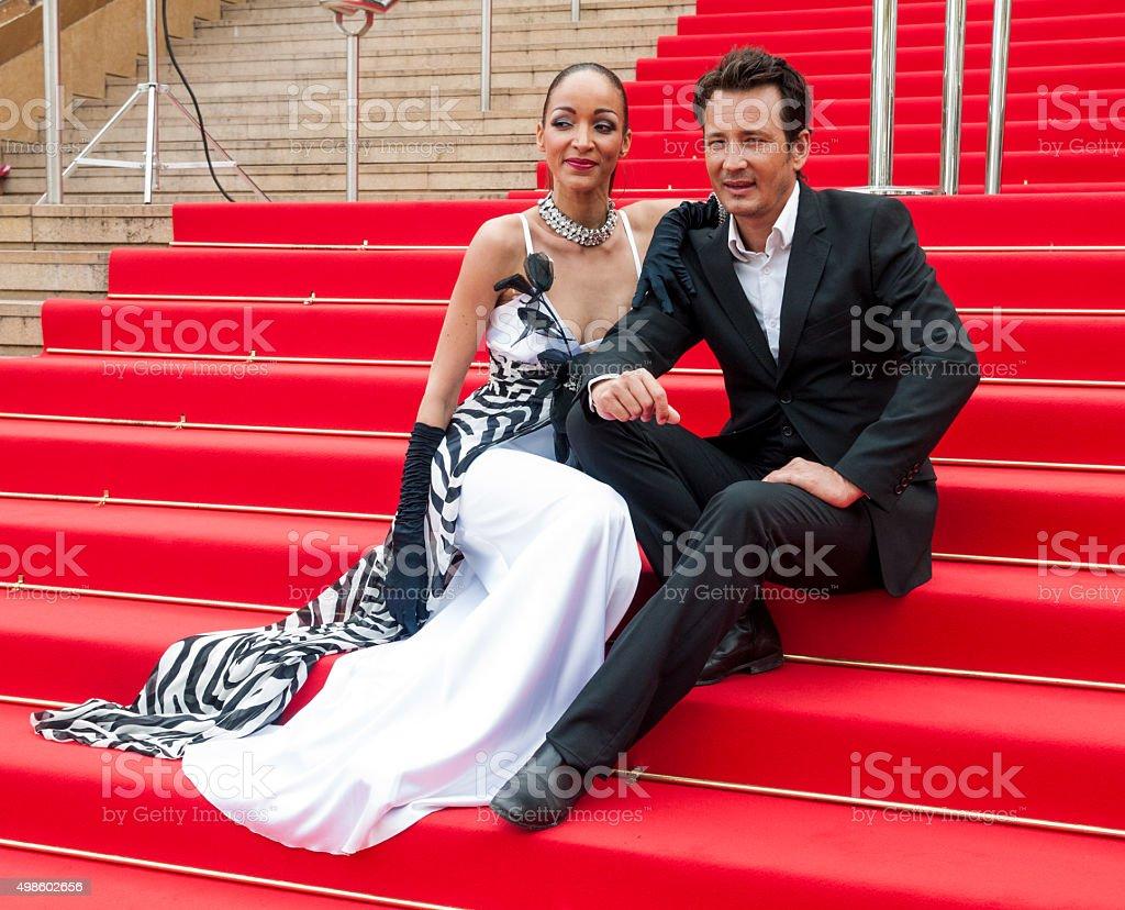 Glamorous couple sitting on the red carpet stock photo