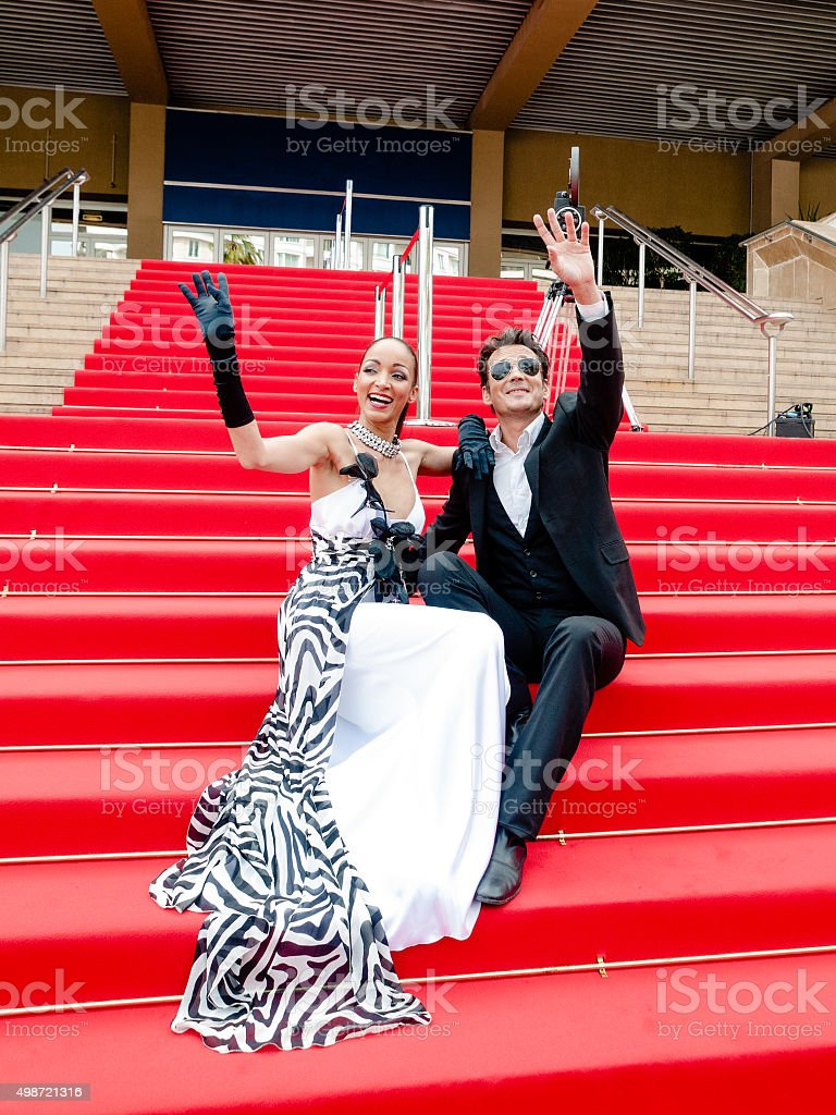 Glamorous couple sitting on the red carpet while waving stock photo