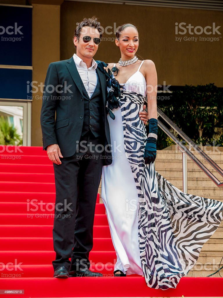 Glamorous couple standing on the red carpet stock photo