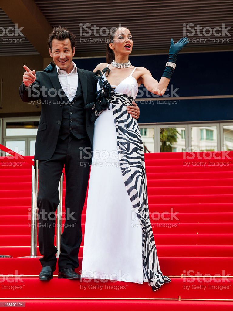 Glamorous couple waving and standing on the red carpet stock photo