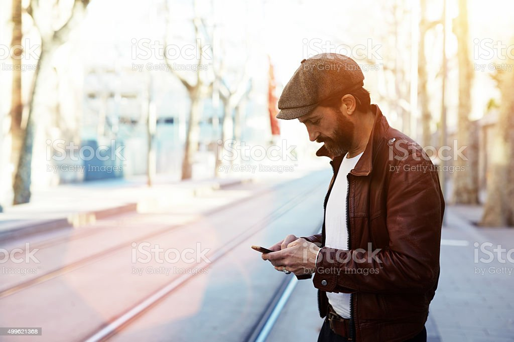 Glamorous male with cool style use smart phone during strolling stock photo