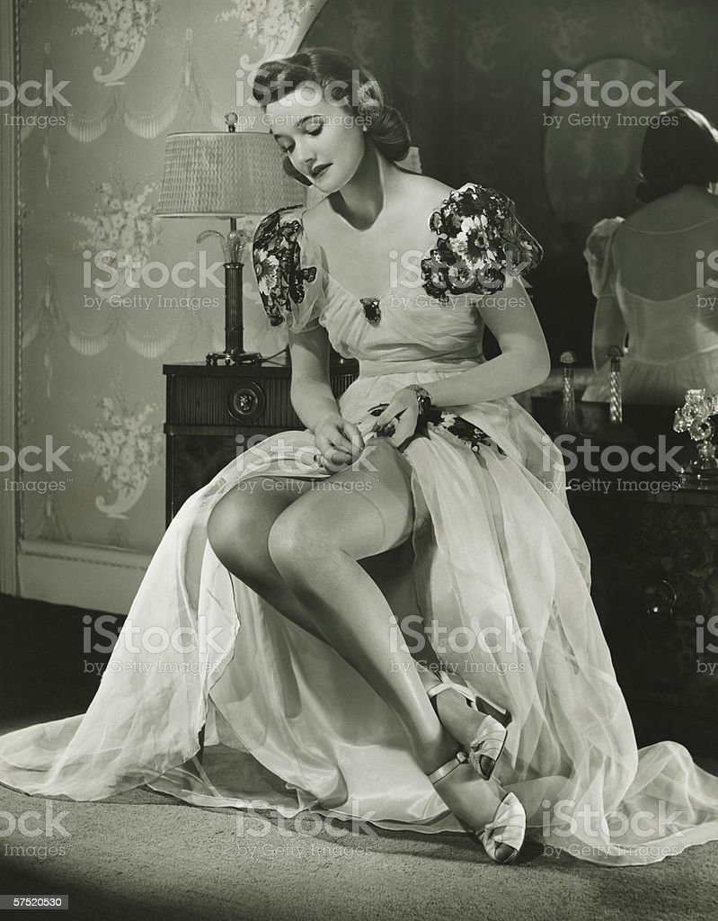 Glamorous woman in evening gown adjusting stockings, portrait, (B&W) stock photo