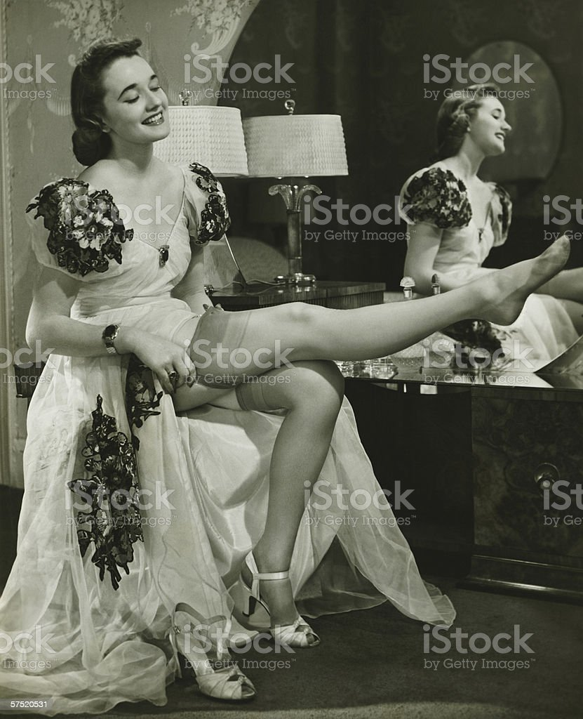 Glamorous woman in evening gown putting on silk stockings, (B&W) stock photo