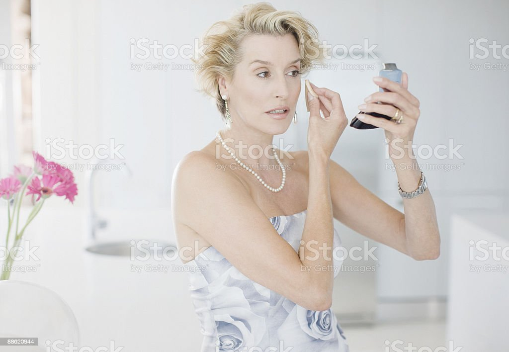 Glamorous woman putting on makeup stock photo