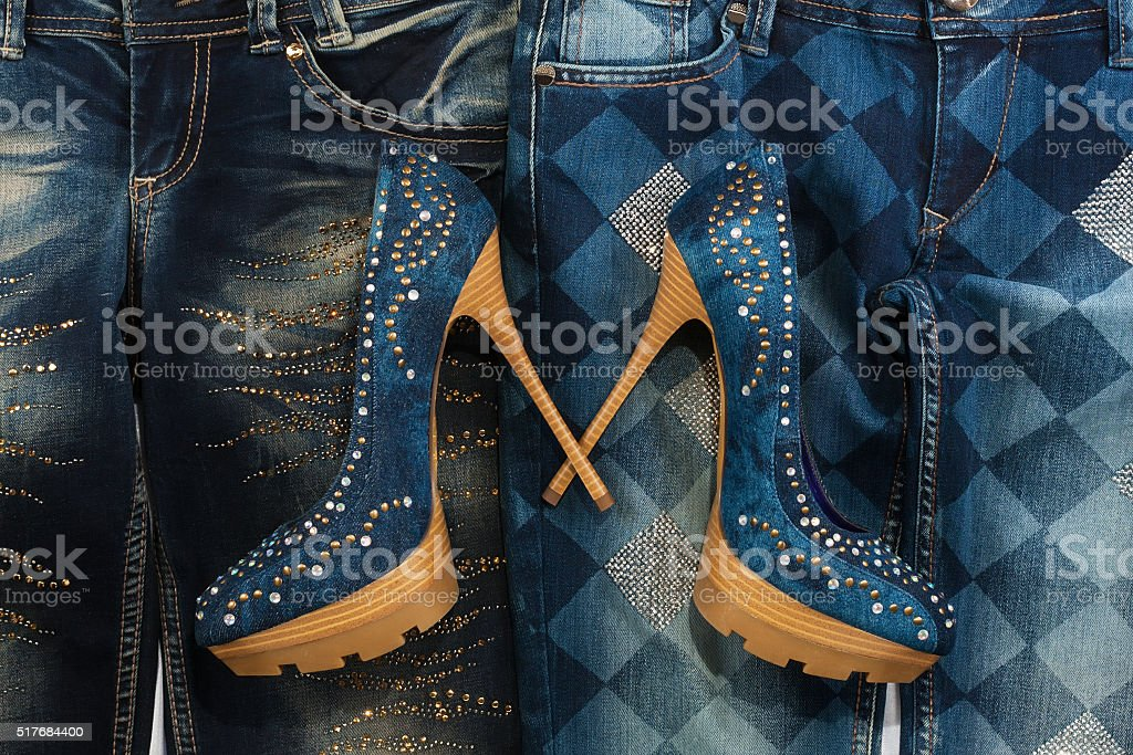 Glamorous women's fashion, jeans, shoes in rhinestones, lying on jeans stock photo