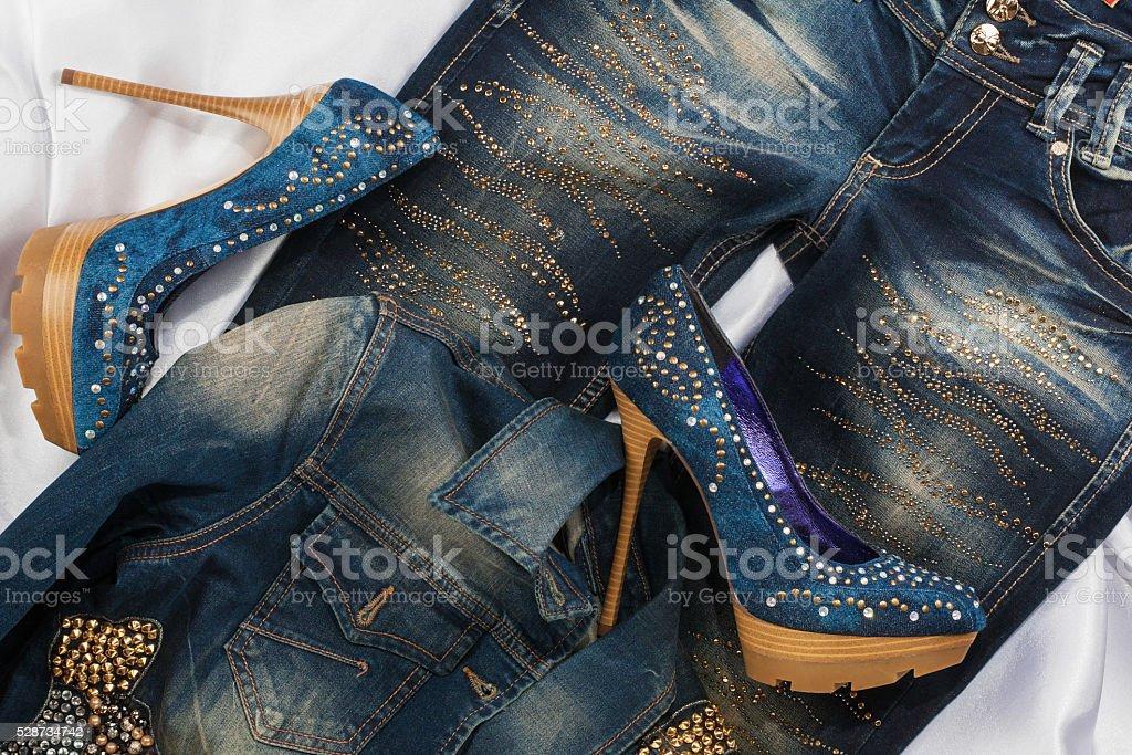 Glamorous women's fashion, shoes in rhinestones, lying on jeans stock photo