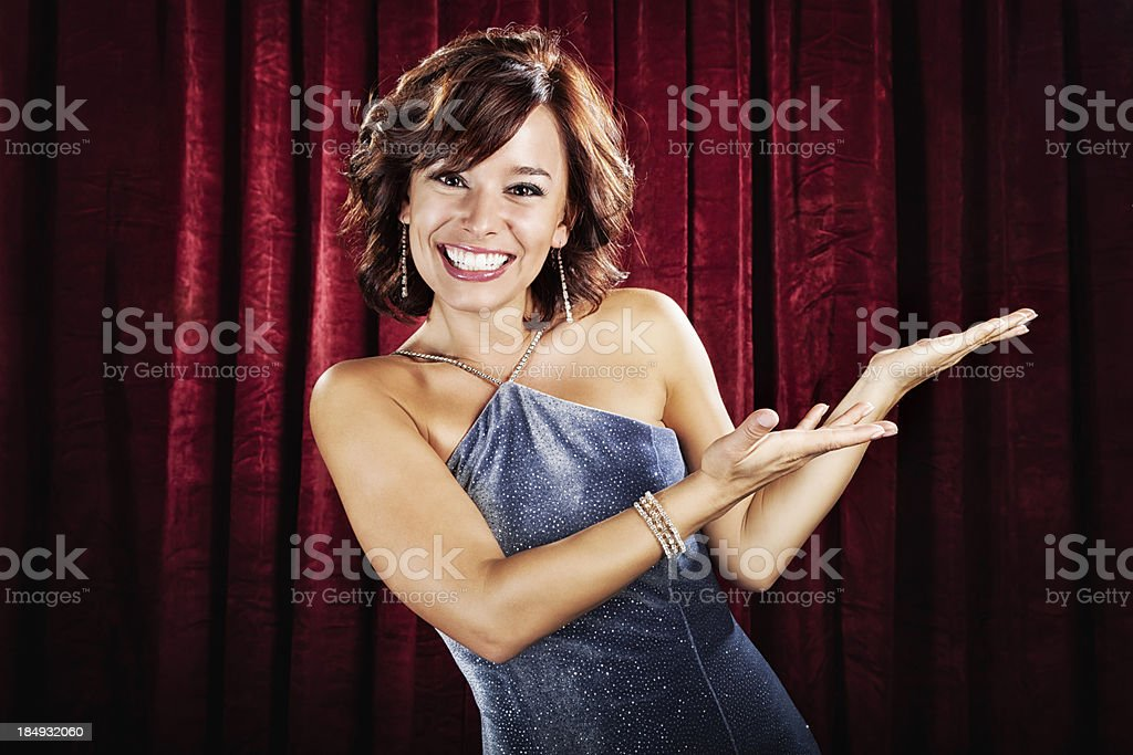 Glamorous Young Woman Presenting at Red Curtain stock photo