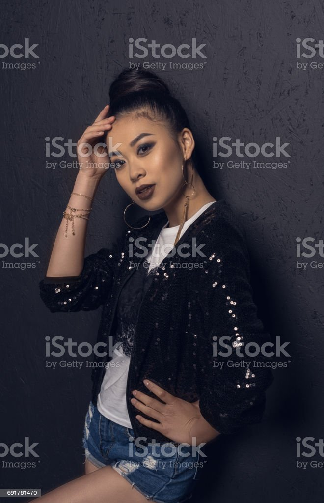 glamour attractive asian disco girl gesturing and posing at grey wall in studio stock photo