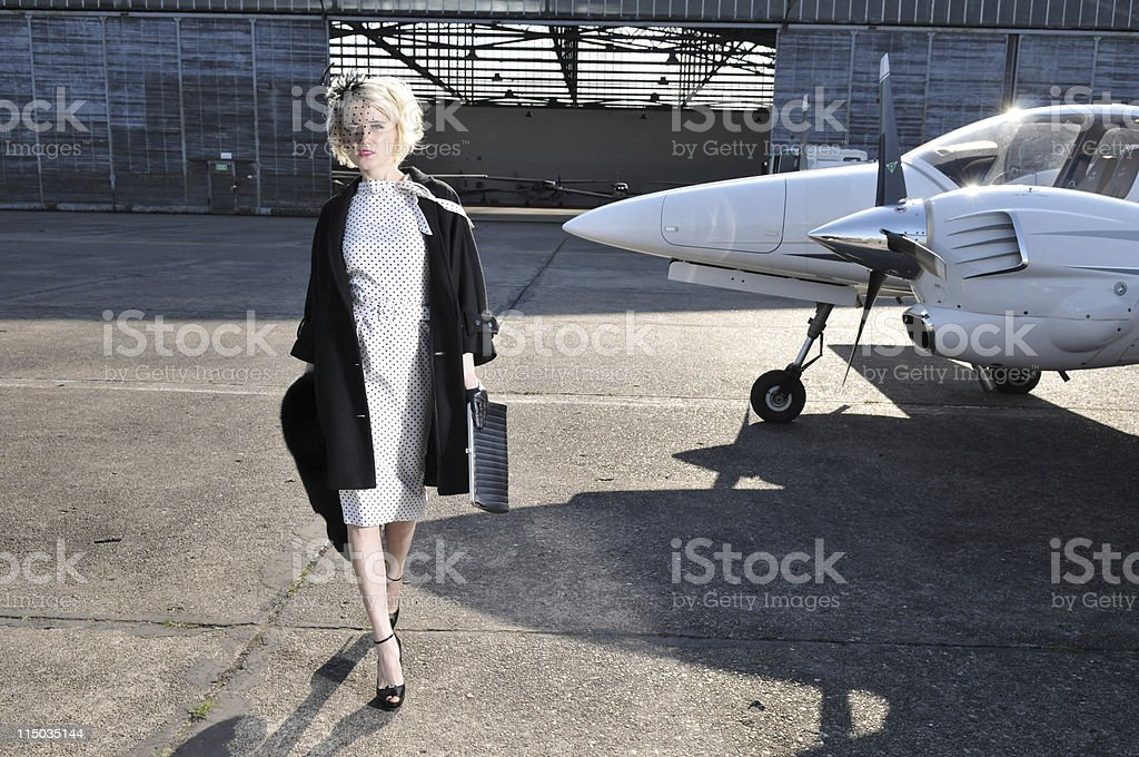 Glamour blond woman in front of plane. stock photo