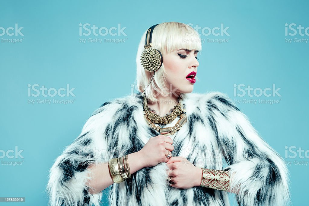 Glamour blonde woman wearing fur jacket and gold jewlery stock photo