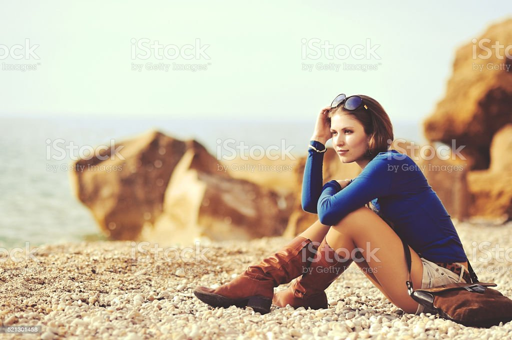 glamourous portrait of the young beautiful woman in leather boots stock photo