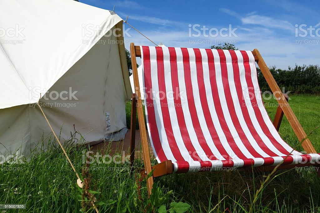 Glamping camping tent deck chair summer field sunny day stock photo