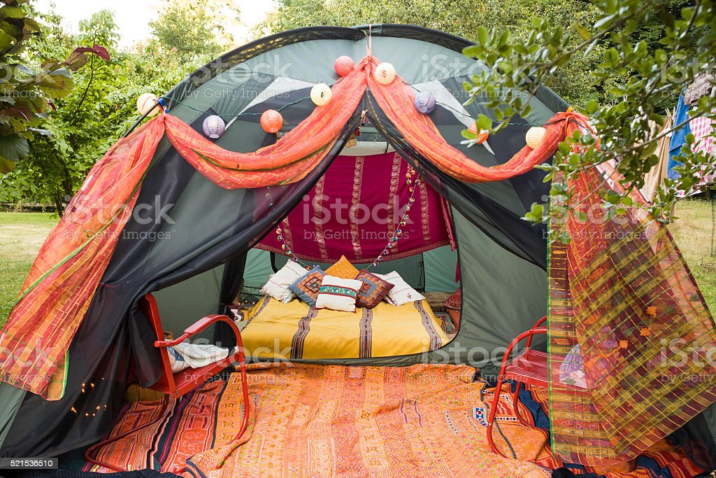 'Glamping' tent decorated with colorful pillows and blankets stock photo