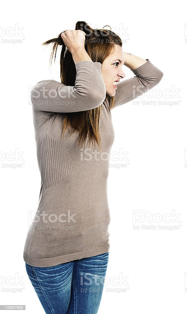 Glaring, furious young woman snarls, tearing hair out royalty-free stock photo