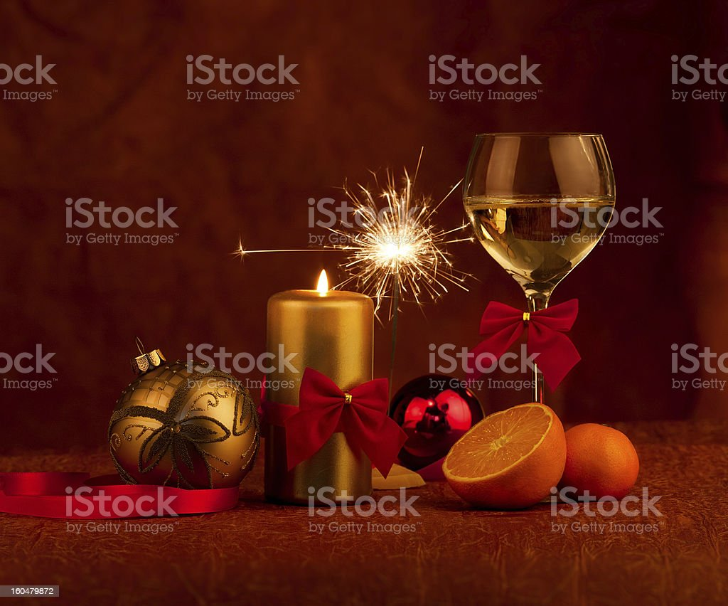 Glas with champagne and burning candle new year balls stock photo