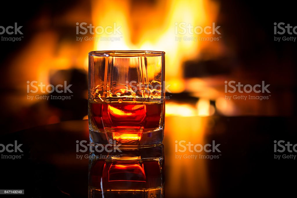 Glass alcoholic drink wine in front warm fireplace. stock photo