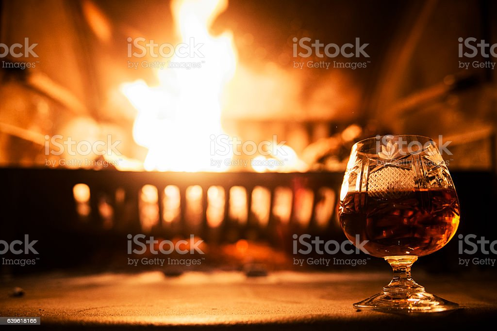 Glass alcoholic drink wine in front warm fireplace stock photo